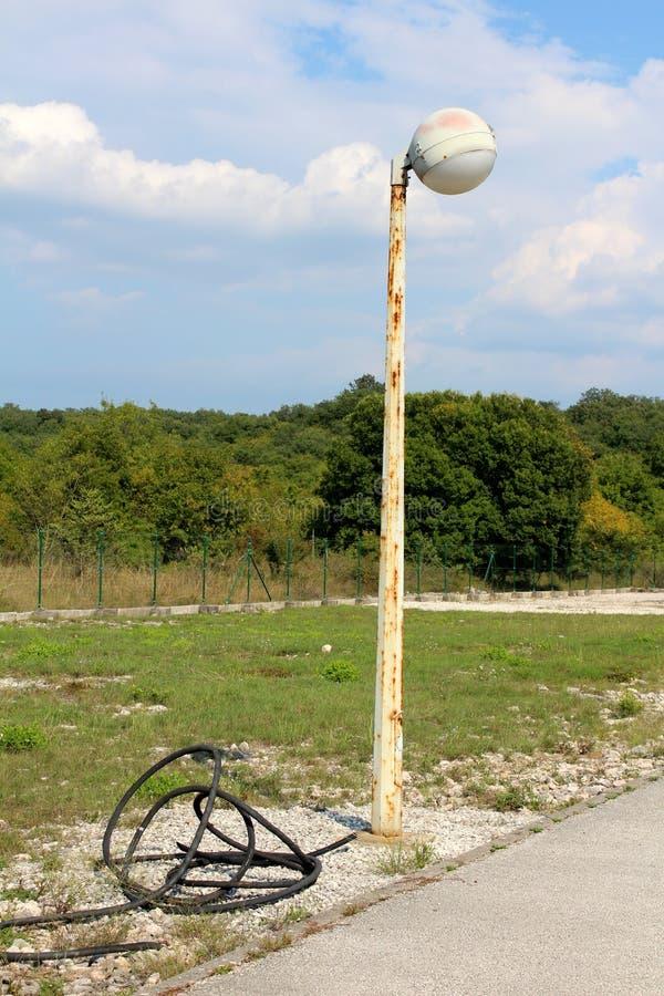 Lámpara de calle en la forma de la bola blanca montada en el polo viejo aherrumbrado del metal rodeado con el alambre eléctrico d imagen de archivo libre de regalías
