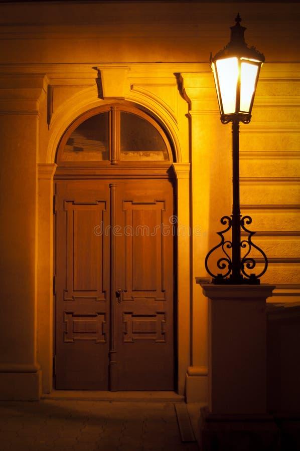 Lámpara de calle en la noche con la puerta imagenes de archivo