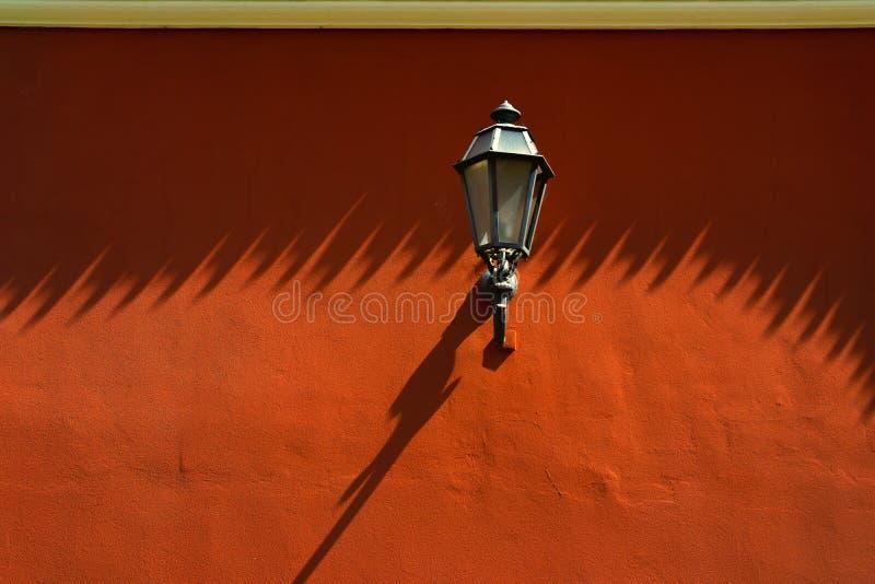Lámpara de calle en la pared roja imágenes de archivo libres de regalías