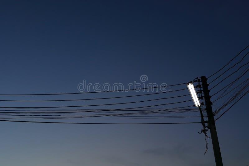 Lámpara de calle en los posts de la electricidad con el cielo nocturno foto de archivo