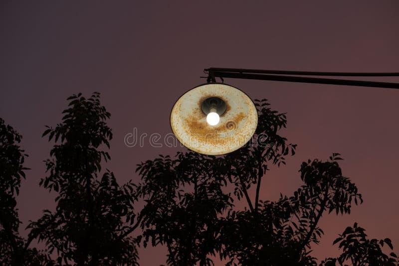 Lámpara de calle oxidada vieja contra fondo hermoso del cielo de la puesta del sol fotos de archivo
