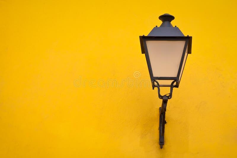Lámpara de calle vieja en una pared amarilla imagenes de archivo