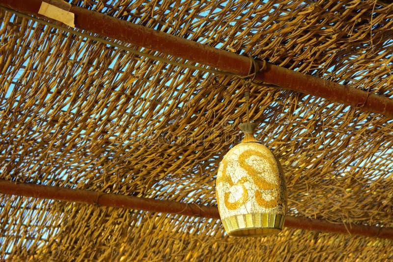 Lámpara de calle vieja polvorienta en el estilo árabe, colgando del techo debajo de un toldo de madera de mimbre imagen de archivo