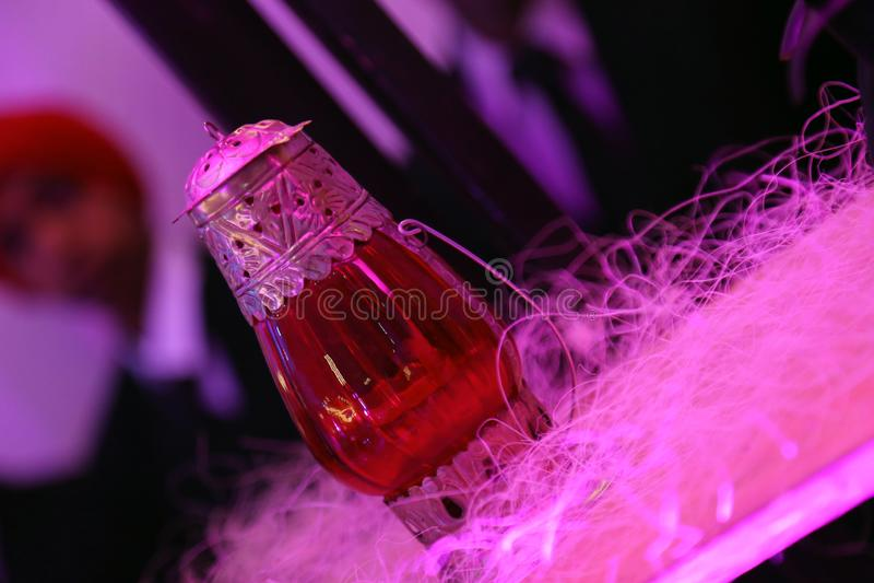 Lámpara de cristal roja con el trabajo del metal aislado con el fondo de la falta de definición foto de archivo
