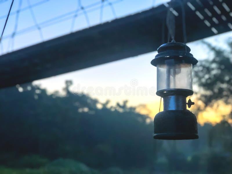 Lámpara de huracán que cuelga en acampar con puente colgante, lámpara con el fondo de la puesta del sol imagen de archivo
