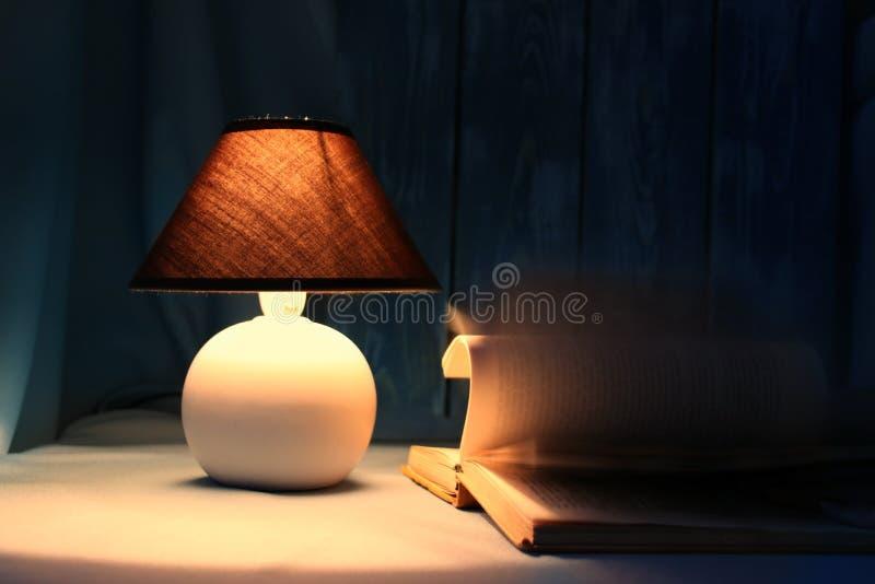 lámpara de la Aún-vida con un libro en una tabla imagen de archivo