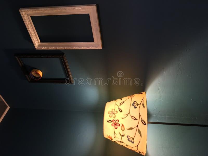 Lámpara de la flor del Lit en la esquina con los marcos vacíos en la pared con un cenicero en uno de ellos foto de archivo