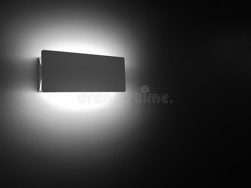 lámpara de la pared que brilla intensamente brillantemente en la oscuridad - lámpara llevada - decoración interior foto de archivo