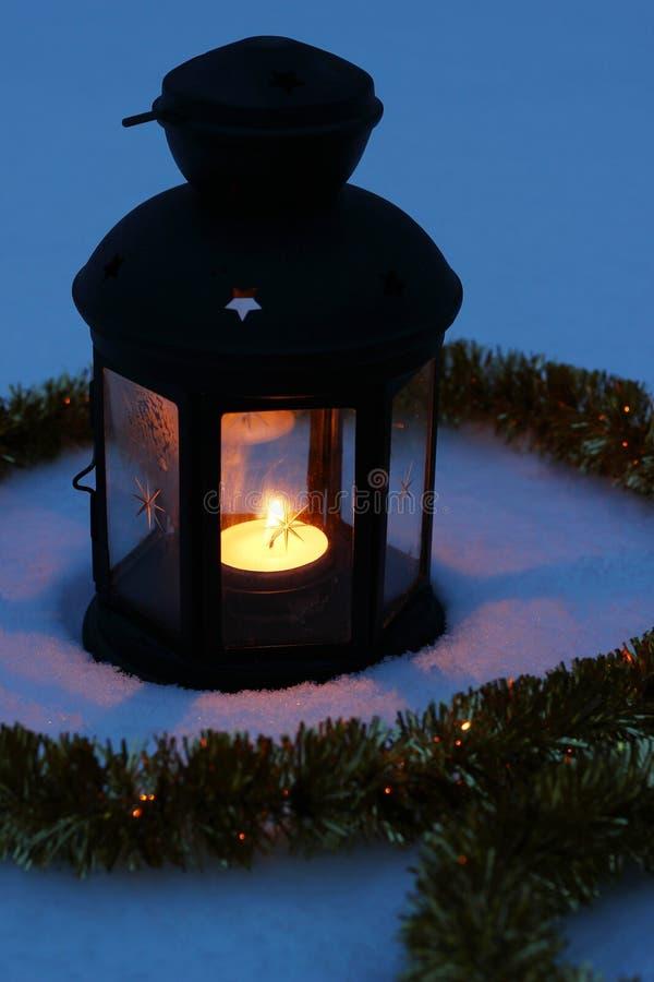 Lámpara de la vela en nieve en la oscuridad imagenes de archivo