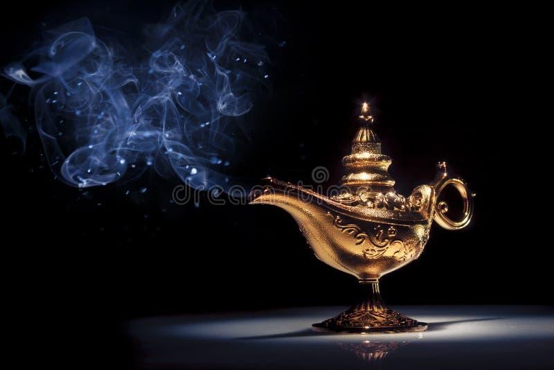 Lámpara de los genios de Aladdin mágico en negro con humo fotografía de archivo