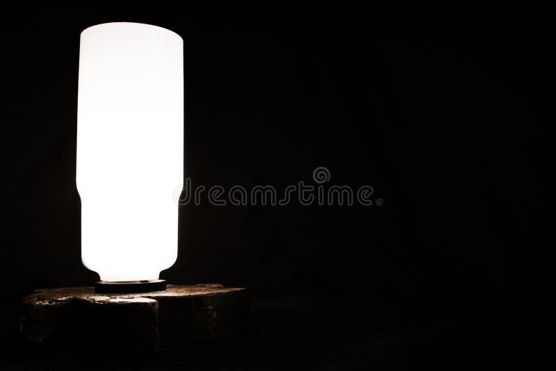 Lámpara de mesa en un fondo oscuro foto de archivo