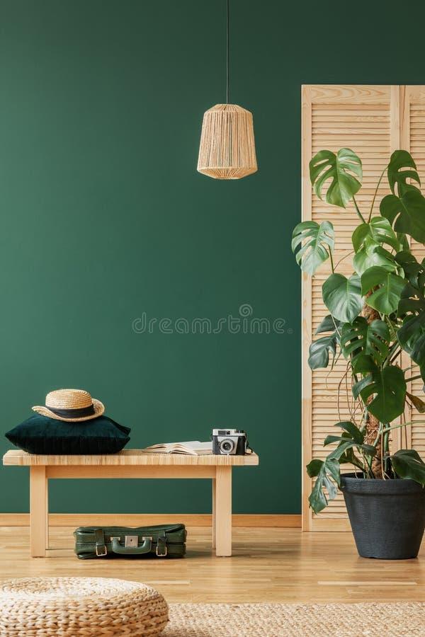 Lámpara de mimbre sobre banco de madera con la almohada verde esmeralda y el sombrero, espacio de la copia en la pared verde vací fotos de archivo libres de regalías