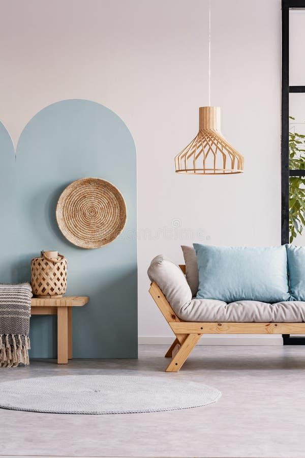 Lámpara de mimbre sobre el sofá escandinavo de madera con el futon en interior brillante de la sala de estar foto de archivo