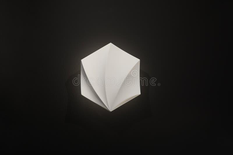 Lámpara de pared, blanca con la luz suave en un fondo negro, forma interesante y hecho del material ligero fotos de archivo