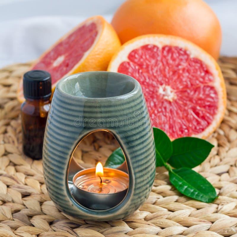 Lámpara del aroma con aceite esencial del pomelo en la estera tejida, pomelos en el fondo, formato cuadrado fotografía de archivo