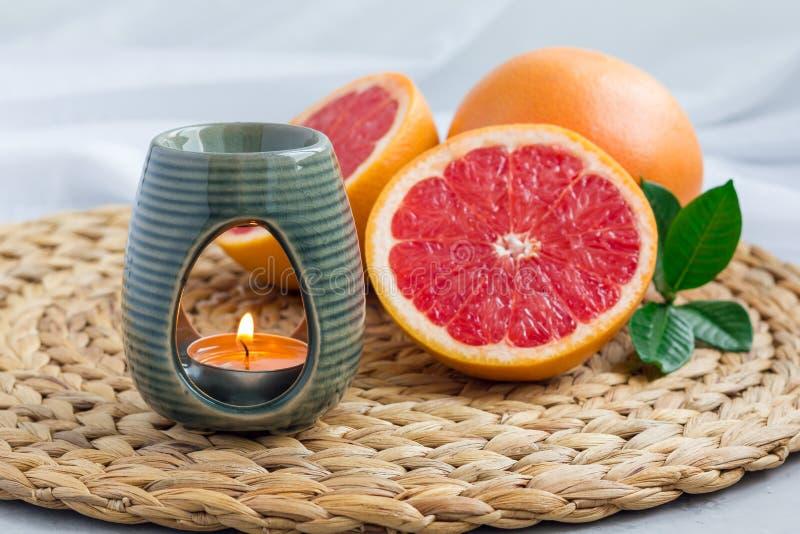 Lámpara del aroma con el aceite esencial del pomelo, fondo del balneario, horizontal fotografía de archivo libre de regalías