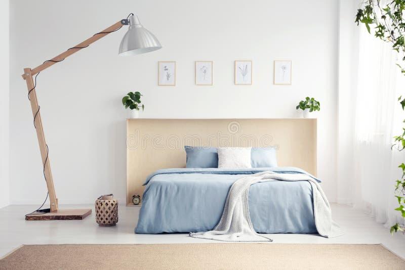 Lámpara del diseñador al lado de la cama azul con la manta en el dormitorio blanco internacional imagen de archivo libre de regalías