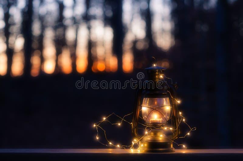 Lámpara del vintage con una vela y las luces en la noche fotos de archivo