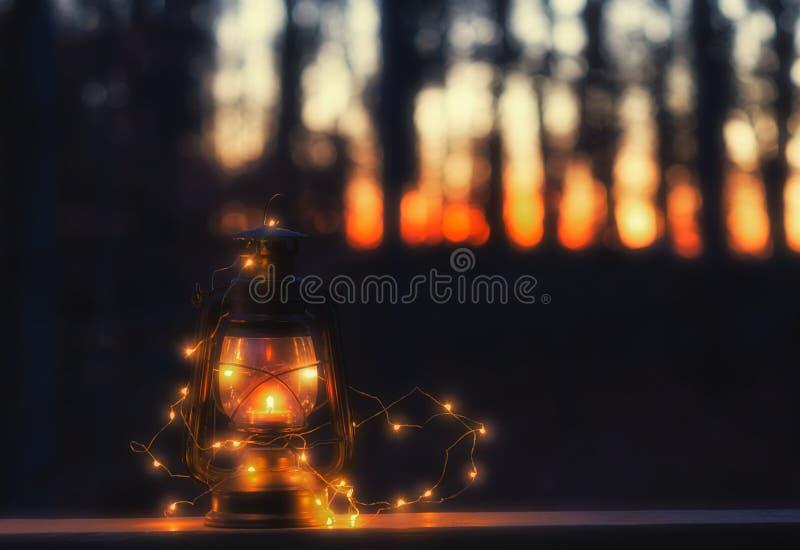 Lámpara del vintage con una vela y las luces en la noche fotografía de archivo