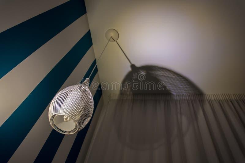 Lámpara elegante del techo al lado de la pared blanca azul con la cortina fotos de archivo libres de regalías