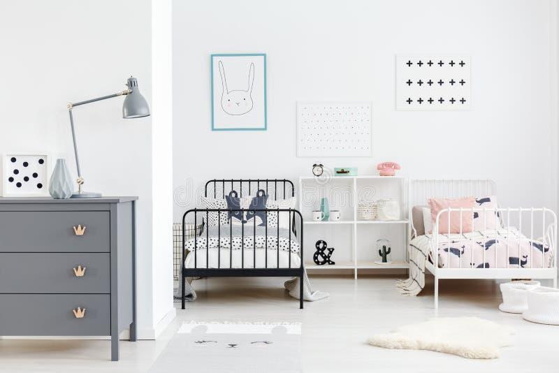 Lámpara en el gabinete gris en interior del dormitorio de los niños con los carteles arriba fotos de archivo libres de regalías