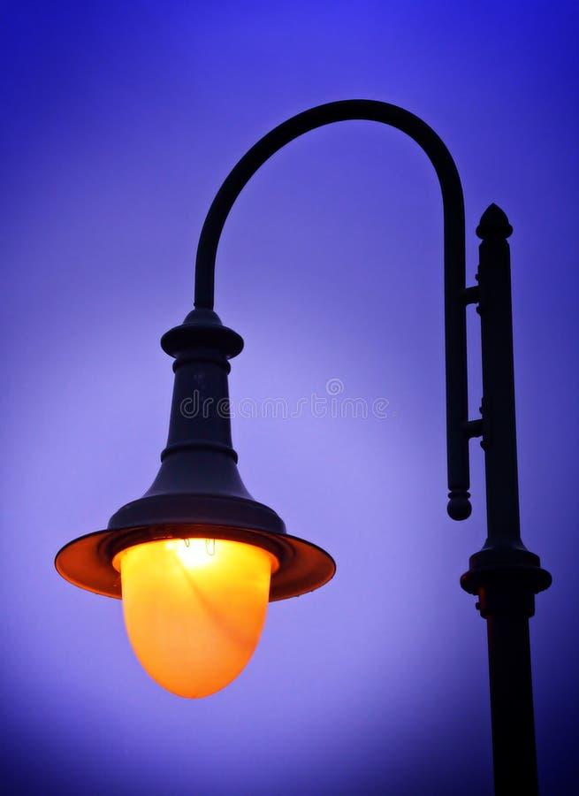 Lámpara encendida con una luz caliente en el crepúsculo del invierno imagenes de archivo