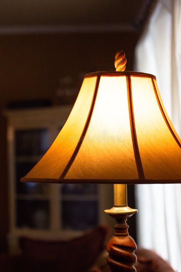 Lámpara iluminada con la sombra en un cuarto oscuro encendido imagen de archivo