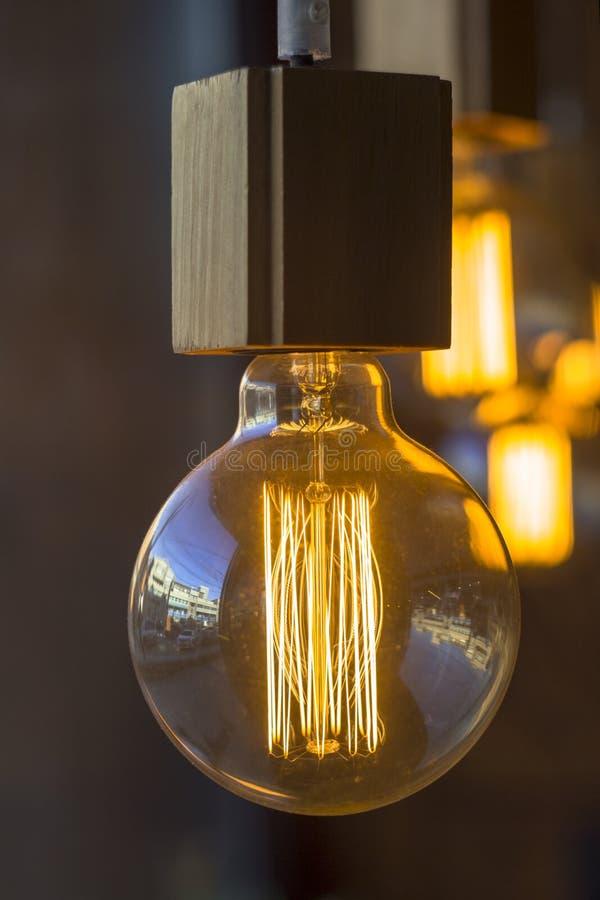 L?mpara incandescente colgante de edison del vintage retro de la ronda que brilla intensamente contra una pared oscura borrosa y  imagen de archivo