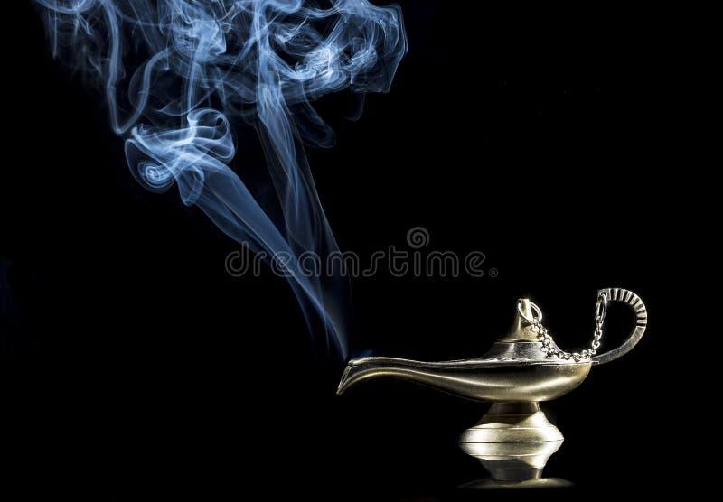Lámpara mágica en fondo negro de la historia de Aladdin con los genios que aparecen en el concepto azul del humo para desear, la  foto de archivo