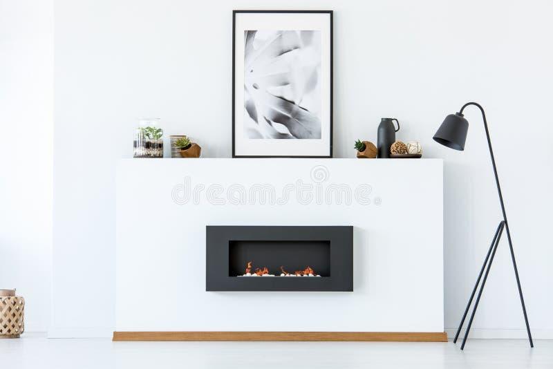 Lámpara negra al lado de la chimenea y del cartel en la vida mínima blanca fotos de archivo libres de regalías