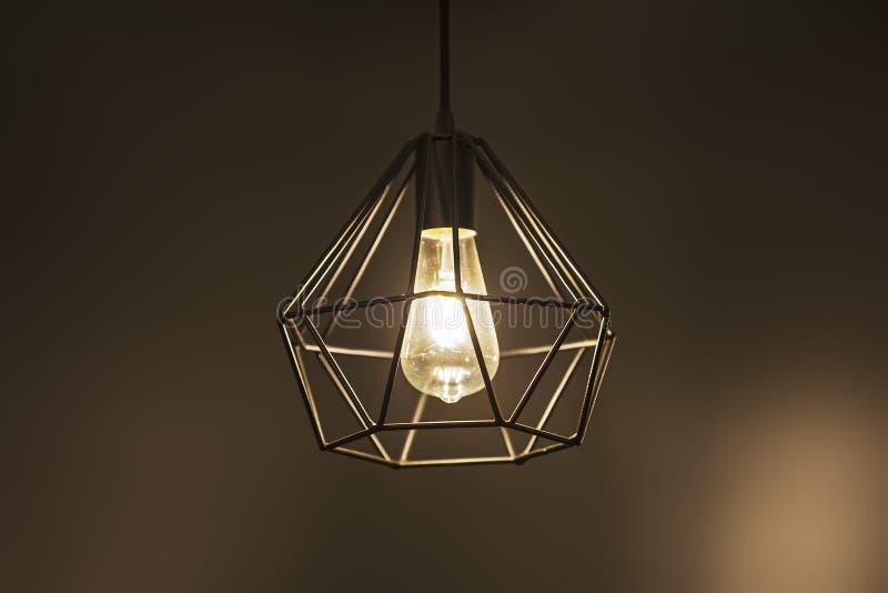 Lámpara pendiente de la lámpara geométrica, lámpara moderna negra metálica, en un fondo caliente marrón imagenes de archivo