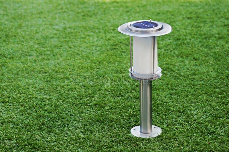 Lámpara por energía solar en fondo de la hierba verde. fotos de archivo