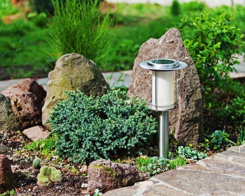 Lámpara por energía solar en fondo del jardín fotos de archivo