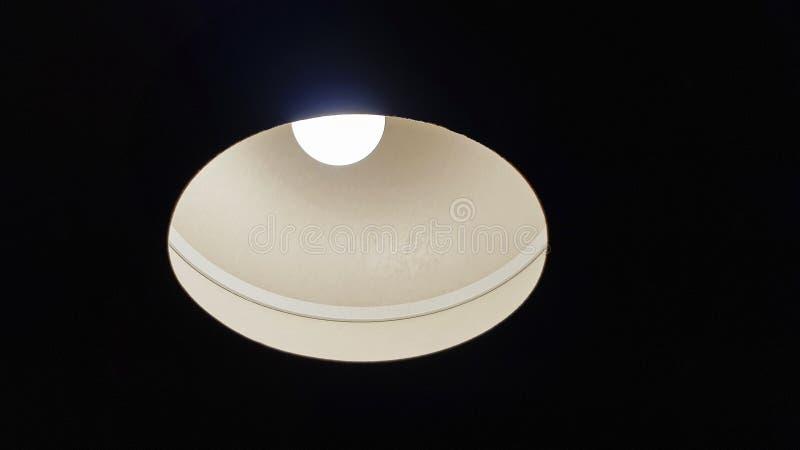 Lámpara que brilla intensamente en tono oscuro La luz brilla abajo fotografía de archivo libre de regalías