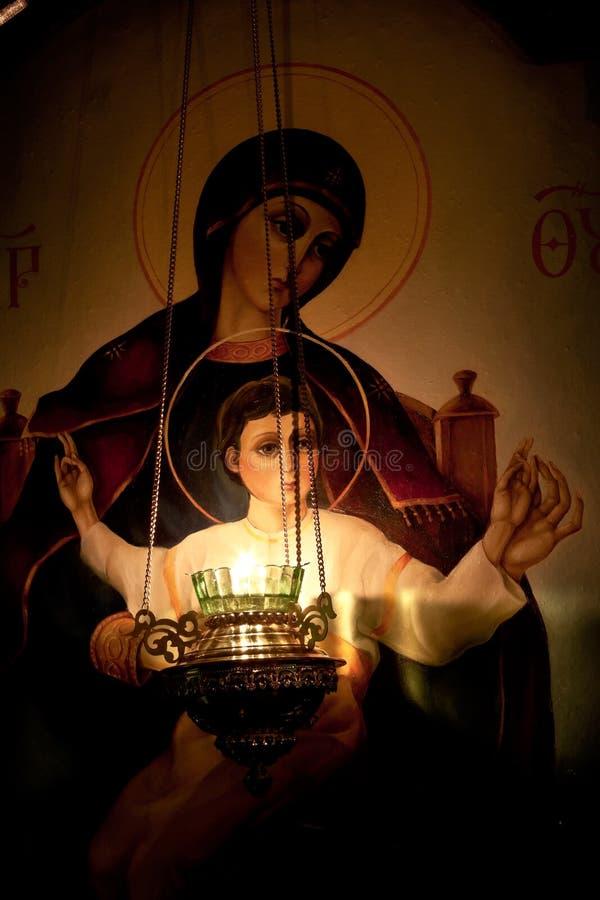 Lámpara que quema antes del icono de nuestra señora imagen de archivo