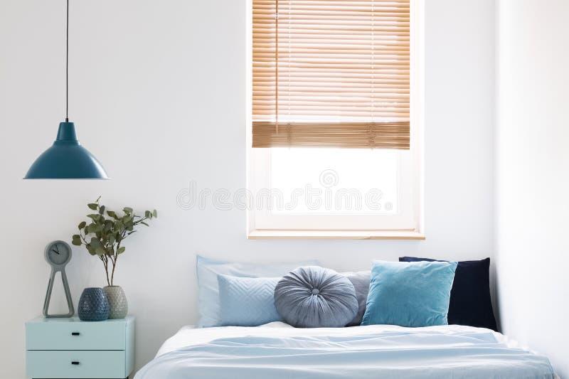 Lámpara sobre el gabinete azul con la planta al lado de la cama en dormitorio simple imagen de archivo libre de regalías