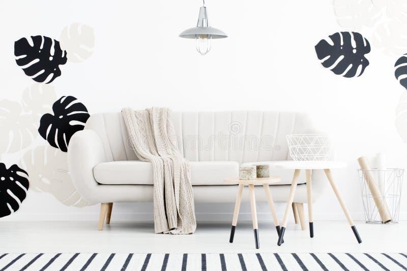 Lámpara sobre el sofá blanco con la manta en interior de la sala de estar con fotografía de archivo