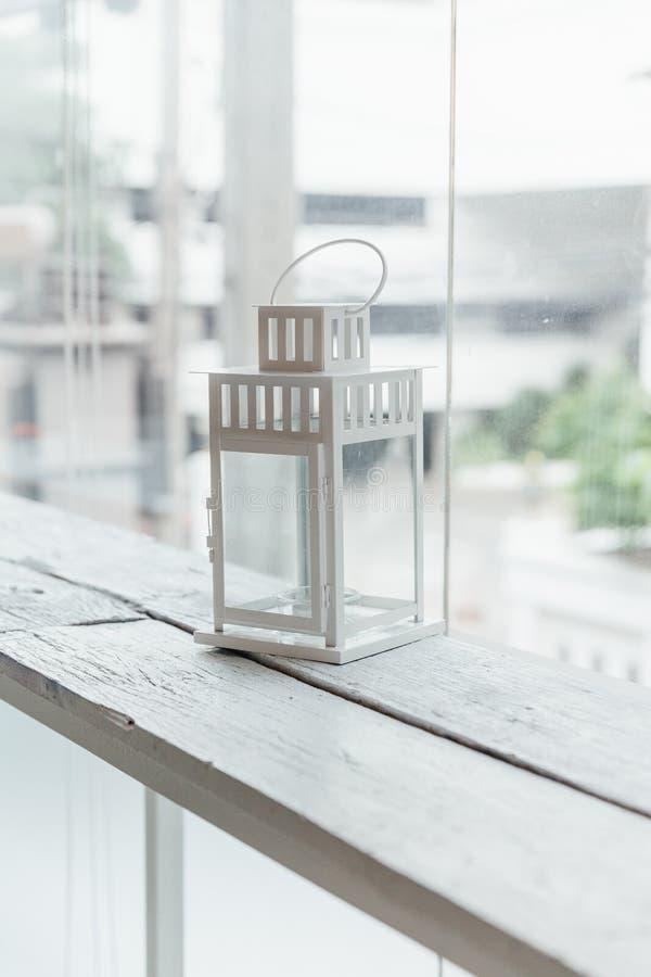 Lámpara vieja blanca en la tabla de madera pintada blanca con la ventana de cristal y árboles en fondo fotos de archivo