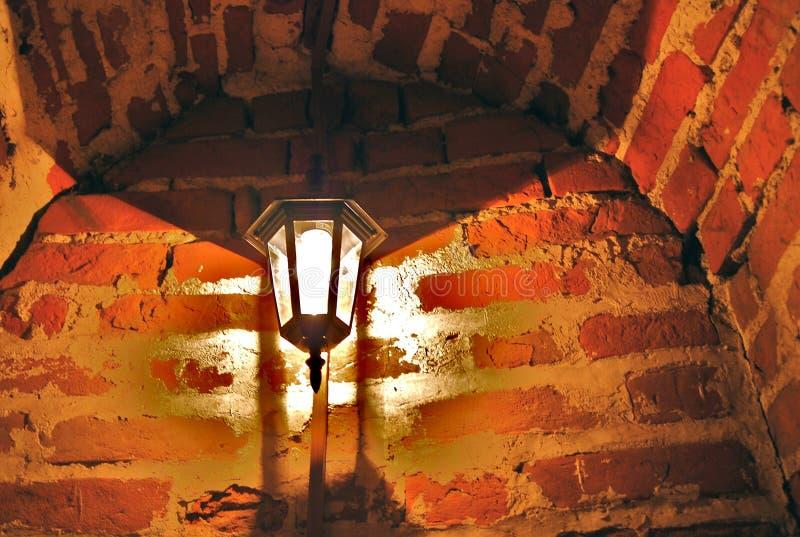 Lámpara vieja en la pared de ladrillos rojos fotos de archivo