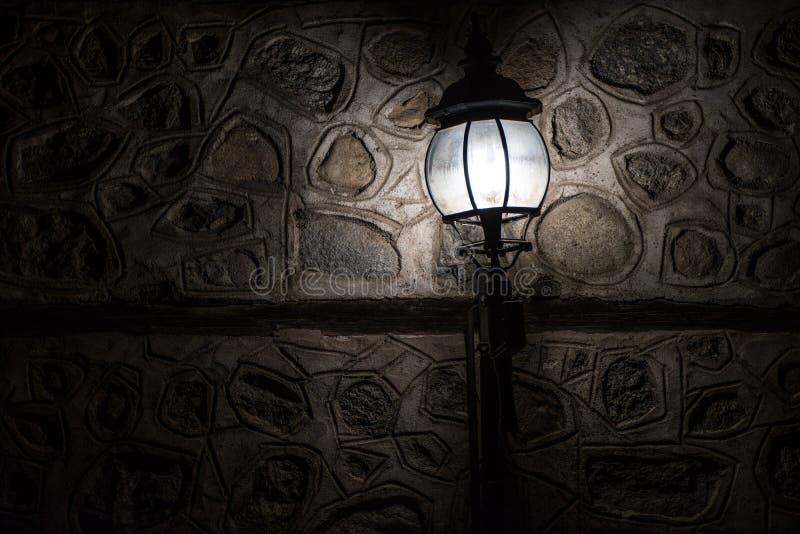 Lámpara vieja que enciende un punto en una pared de piedra fotografía de archivo libre de regalías