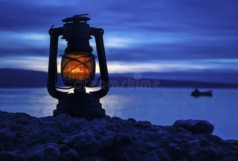 Lámpara y barco viejos en puesta del sol fotografía de archivo