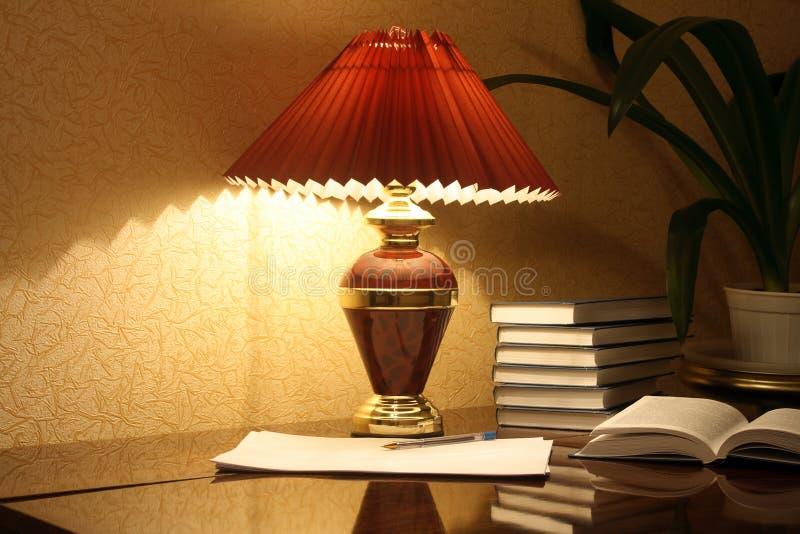 Lámpara y libros foto de archivo