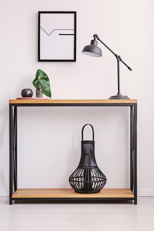 Lámpara y linterna en estantes contra la pared blanca con el cartel en interior plano simple Foto verdadera fotografía de archivo libre de regalías
