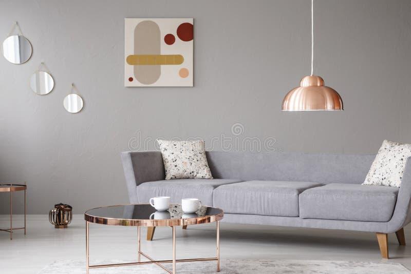 Lámpara y mesa de centro de cobre delante de un sofá moderno en un interior gris de la sala de estar foto de archivo