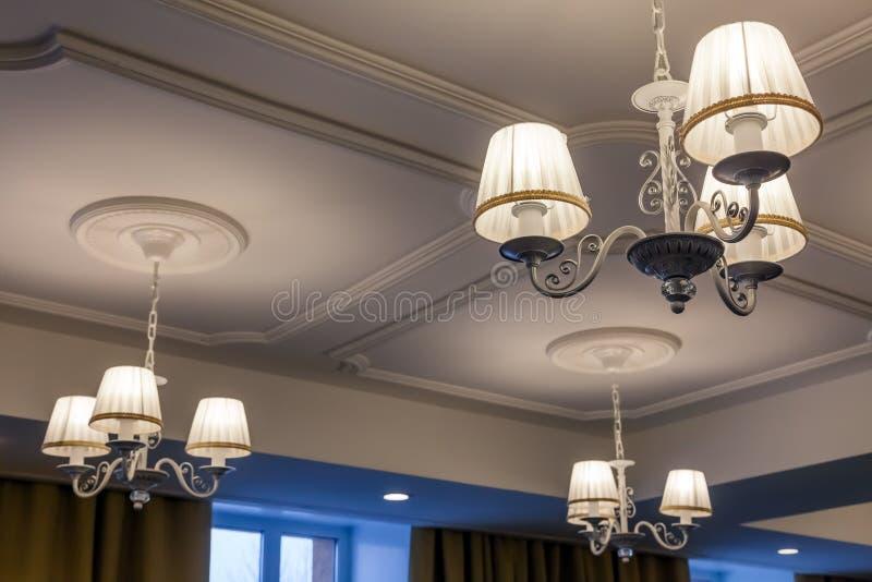 Lámparas con tres lámparas eléctricas y pantallas que cuelgan encendido foto de archivo libre de regalías