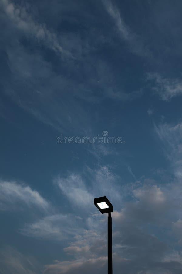 Lámparas de polo ligero encendidas contra el cielo azul marino fotos de archivo