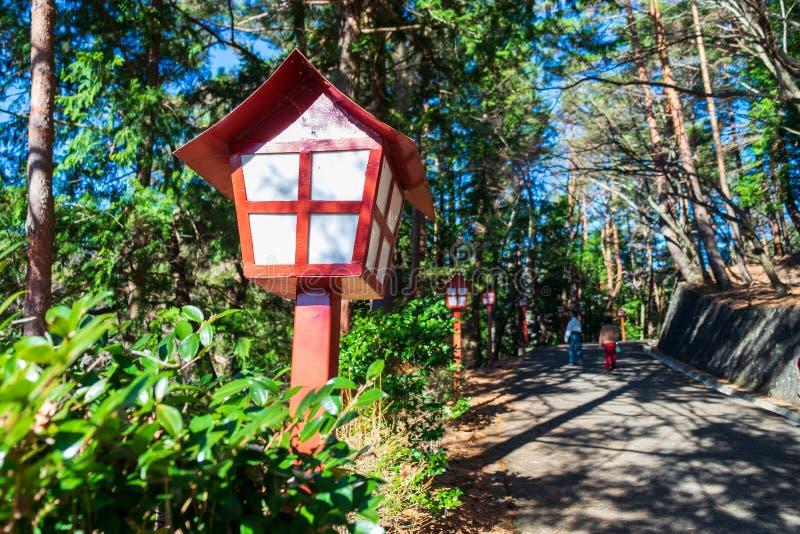 Lámparas japonesas instaladas a lo largo del camino en el jardín o en el bosque imagen de archivo