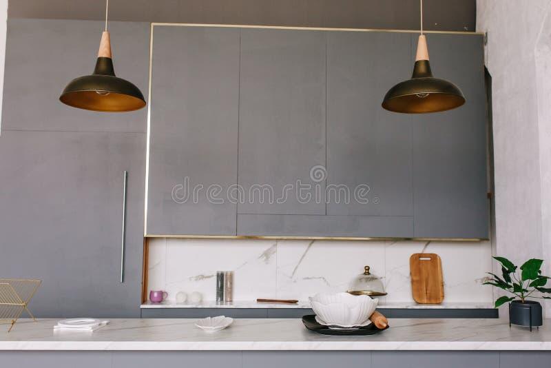 Lámparas negras de la cocina del desván en un estilo moderno con los gabinetes grises, los armarios blancos y los estantes con lo foto de archivo