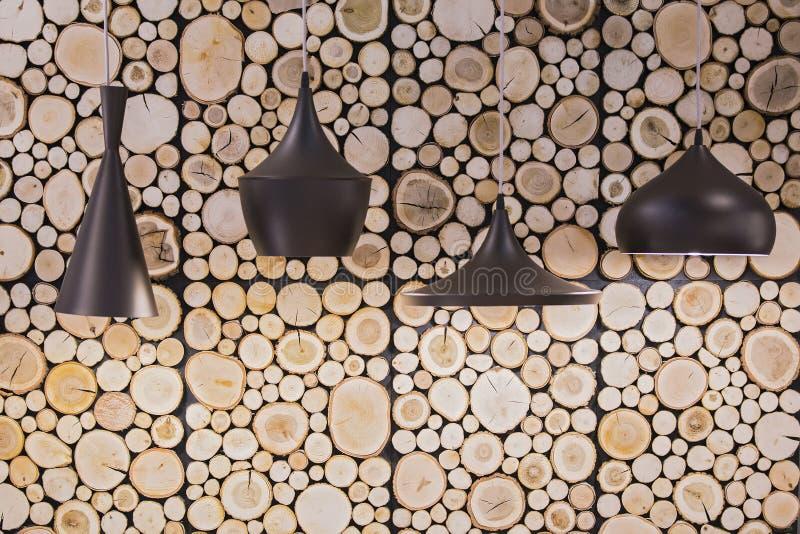 Lámparas negras en una ejecución del café en un fondo de cabañas de madera de madera en la pared imagen de archivo
