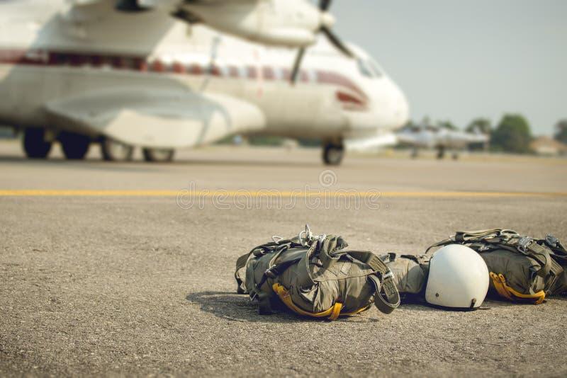 Láncese en paracaídas con el equipo para el paracaidista en el tr de tierra y militar fotos de archivo libres de regalías